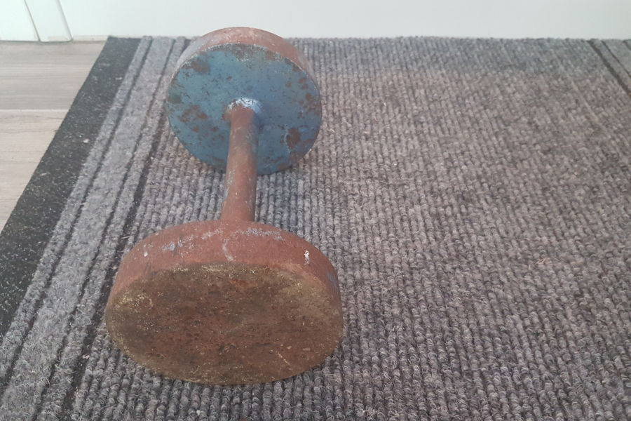 Rusted dumbbell on a carpet.