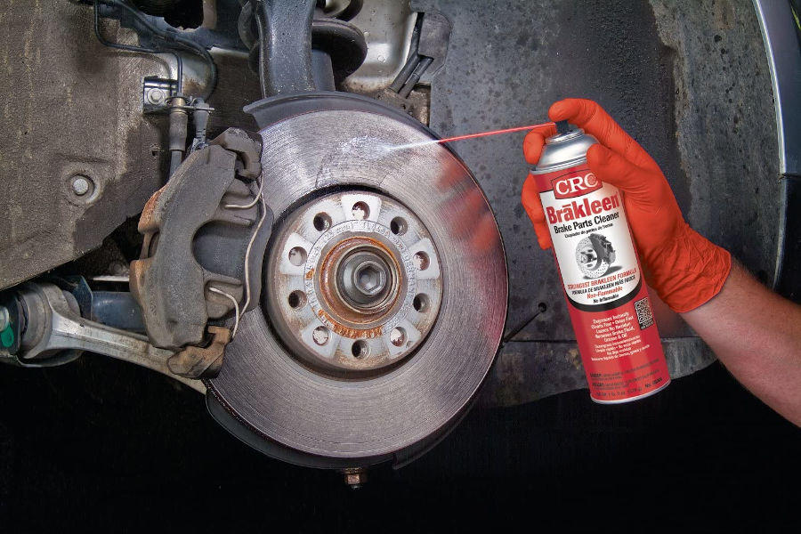 Cleaning brake rotor with a brake cleaner.